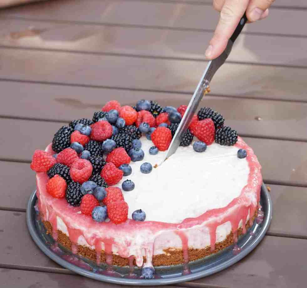 a person slicing into an ice cream cake with pink rhubarb drizzle and mixed berries and an almond cake crust on a picnic table at a BBQ