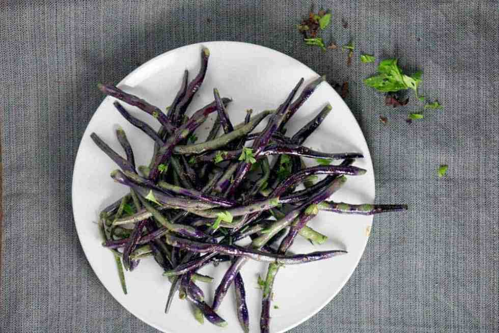 Blistered Purple green beans sauteed with white truffle paste create a purple and green tie-dyed plate that's the perfect savory accompaniment for any dinner.