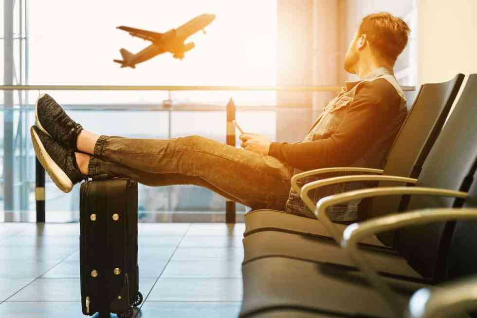Man sitting at sunset with legs over suitcase in airport looking out the window as a plane takes off.