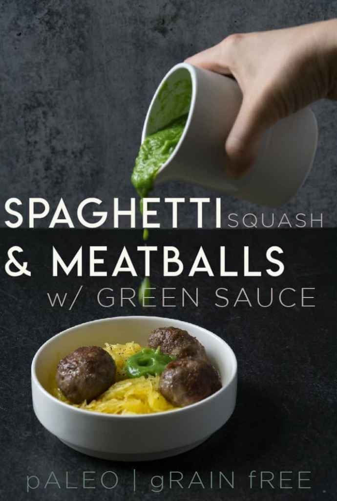 Green sauce dripping onto meatballs on spaghetti squash in white bowl on dark marble and poured concrete surface