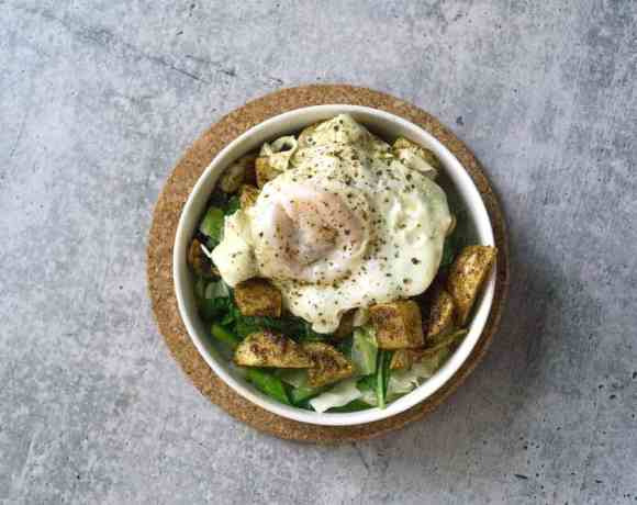 White bowl on cork circle on cement with sauteed cabbage and turnip greens with harissa roasted turnips and broth poached eggs