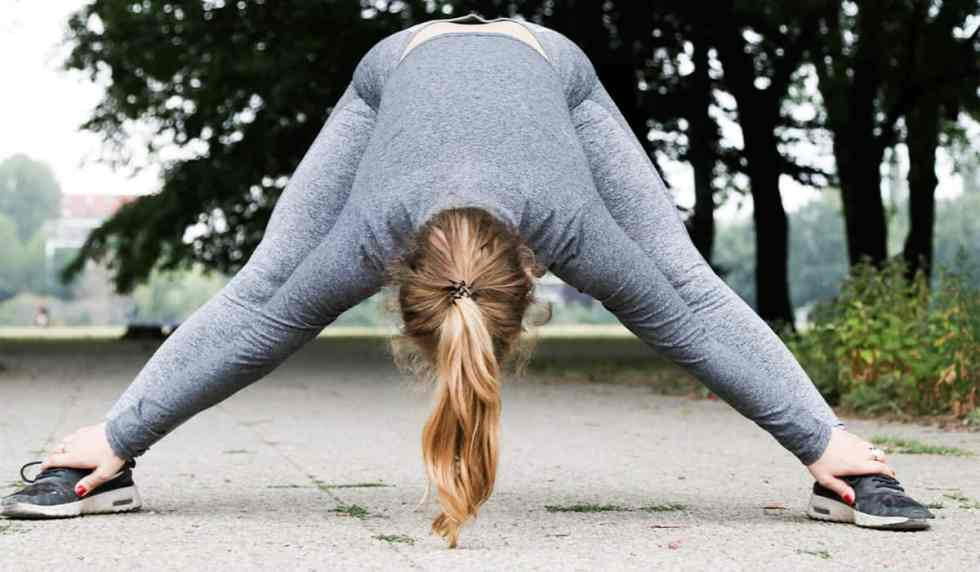 Lady in running clothes in a park stretching, getting ready to exercise to manage fat