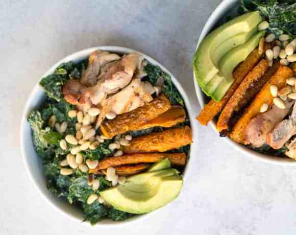 Superfood Kale Caesar salad with avo, chicken thighs, pine nuts, and creamy tahini cashew Caesar dressing
