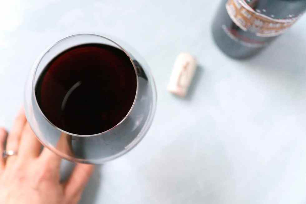 A full bulbous glass of red wine with a bottle and cork