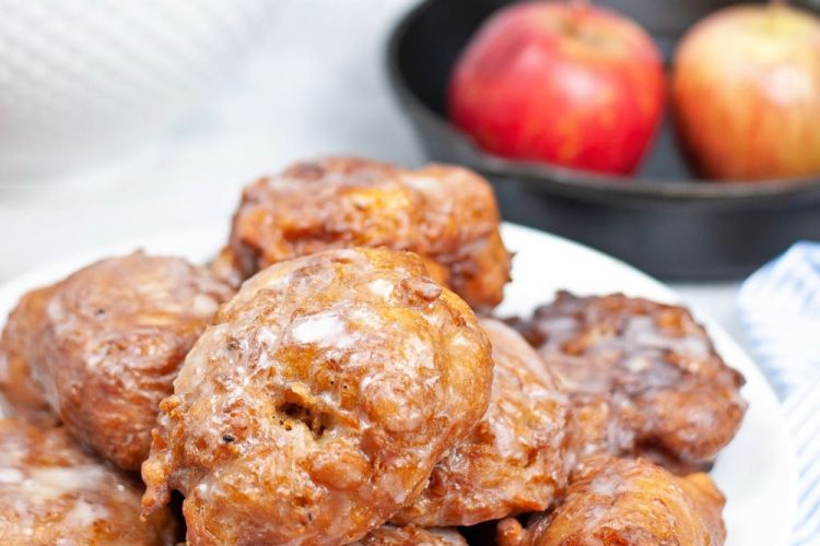 Close up image of fried homemade apple fritters with sugar glaze