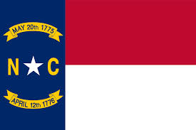 North Carolina state flag with N, C, star, and 2 dates on ribbons on vertical blue stripe left of red and white stripes.