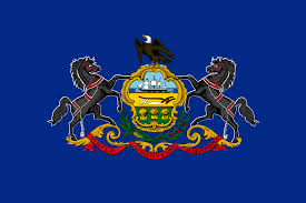 Pennsylvania state flag with coat of arms and state motto; Liberty, Virtue, Independence, on a ribbon on a blue field.