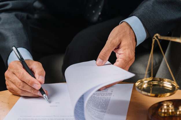 close-up-male-lawyer-signing-contract-document-desk_23-2147898656