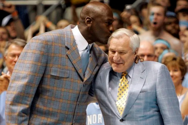 Former North Carolina player Michael Jordan, left, gives his former coach Dean Smith a kiss during halftime of a college basketball game between North Carolina and Wake Forest in Chapel Hill, N.C., Saturday, Feb. 10, 2007. The 1982 and 1957 championship teams were recognized during a halftime ceremony. Jordan was a member of the 1982 team. (AP Photo/Gerry Broome)