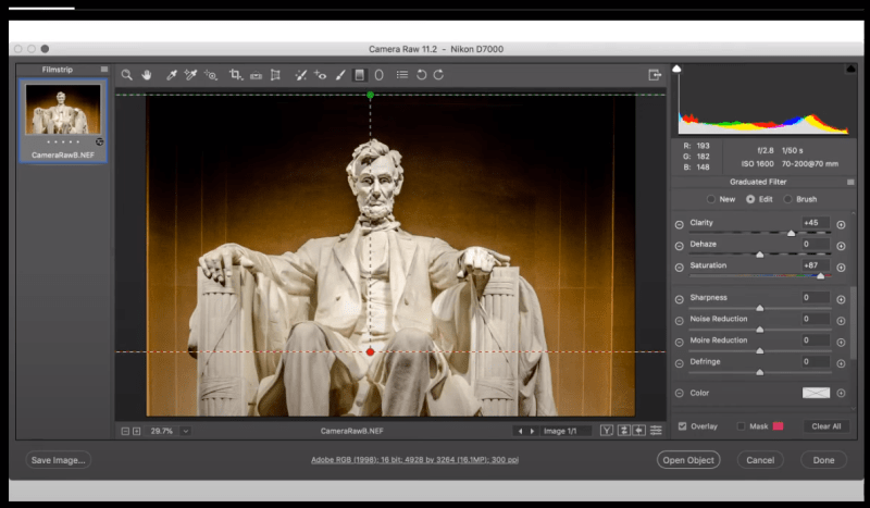 In the image shown, which Camera Raw feature was used to restrict the graduated filter to avoid the statue?