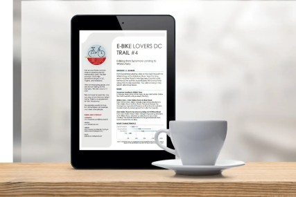 A picture of a cup of tea or coffee with a tablet showing an E-bike Lovers' trail description.