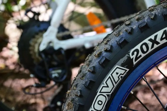 A close-up of a tire with a bicycle frame in the background