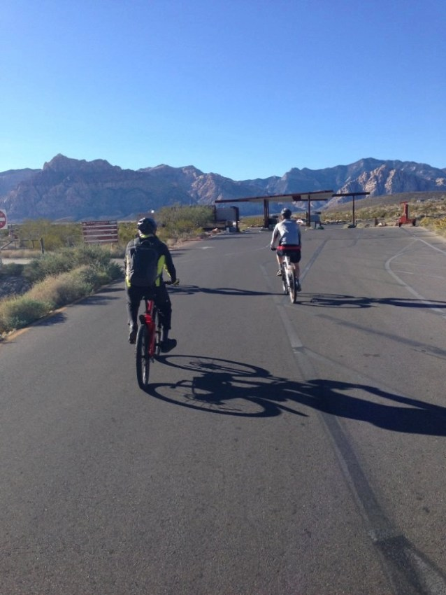 E-bikers in Red Rock State Park, Nevada on a wide asphalt road.