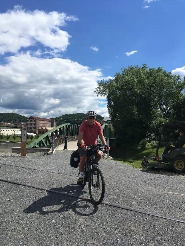 An e-biker in a red shirt ebiking on a sunny day in Washington D.C.