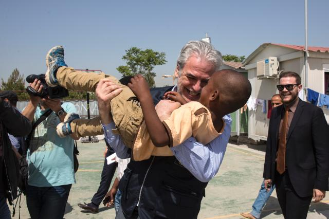 Visit at Elaionas refugee camp:</br> Christos Stylianides carrying a boy