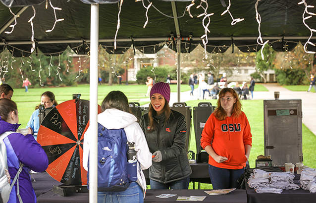 Ali Duerfeldt stands behind a large booth with a prize wheel and large coffee dispensers. She and others around her wear OSU sweaters.