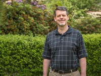 Andy Edwards stands in front of a level green hedge wearing a dark polo with intersecting vertical and horizontal stripes.