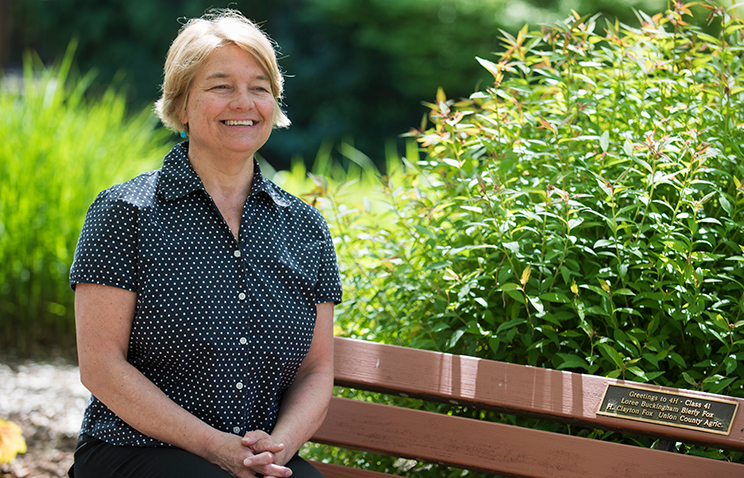Sustainability instructor and double degree program academic advisor Ann Scheerer. She sits on a brown bench with bushes in the background.