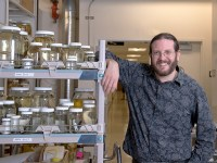 Fisheries and wildlife sciences associate professor Brian Sidlauskas stands next to multiple stacked shelves filled with jars of specimens.