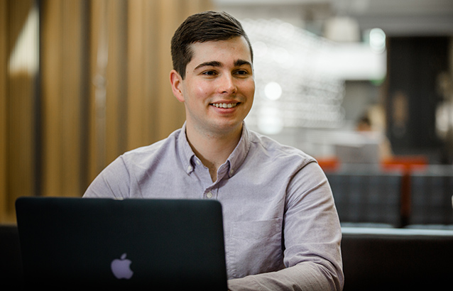 Geoffrey Wildish sits in a study area on campus with his black laptop open in front of him. Geoffrey is earning a business minor on top of his construction engineering management and innovation management degree.