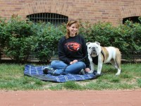 Christine Mosser sits on a blue blanket spread out on the lawn and her bulldog, Chesty, stands next to her.