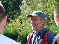 College of Forestry instructor Dave Stemper is addressing a group of students, three of whom are visible, in an outdoor setting with trees in the background. Dave is wearing glasses with thin wire frames, a blue polo, a red vest with pens in the pocket, and a green baseball cap.