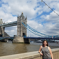 Emily Critelli, a student in the Human Development and Family Sciences program, leans against a cement wall with London's Tower Bridge and the River Thames in the background.
