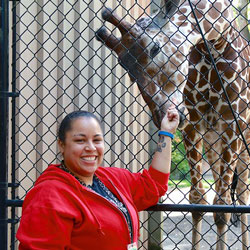 Erin wears a bright red sweatshirt and smiles facing the camera. She holds her left arm up to the black chain link fence behind her, where Bakari the giraffe bends his neck down to eat from her hand.