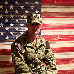 Evan Huegel wears his military uniform in front of a wooden wall that is painted to look like the American flag.