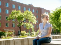 Heather Bell, radiation health physics student, sits outdoors on the OSU Corvallis campus.