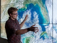A person stands in front of a video wall, looking at satellite imagery of Earth. GIScience online