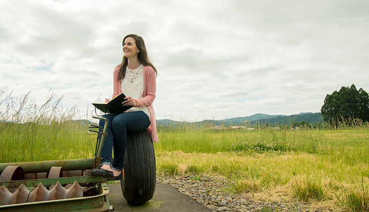Grace Masterjohn holds a notebook and sits on the tire of a piece of farm equipment in the middle of a green field. She wears a white shirt, pink cardigan and blue jeans.