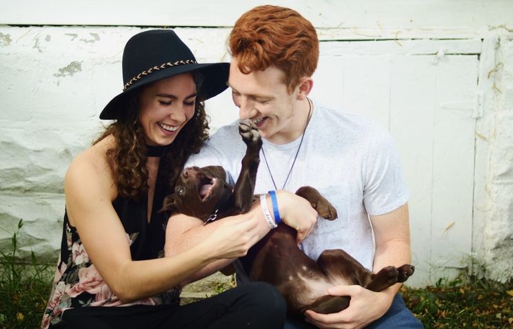 Hannah Thelen is seated outdoors against a white wall. To her right is her husband. The two are holding a puppy with brown fur, which lays on its back in their arms and looks playful with its mouth open and one front paw in the air.