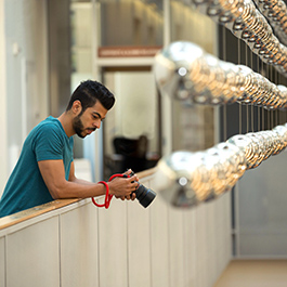 Hussain Al Balushi looks down at his camera's digital display. He stands on an indoor balcony and there are dozens of decorative silver hanging balls.