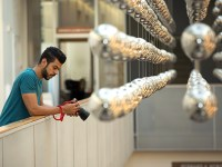 Hussain looks down at his camera's digital display. He stands on an indoor balcony and there are dozens of decorative silver hanging balls.