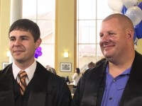 Ian Kassab and Walter Webster stand side-by-side at the Ecampus graduation reception, wearing their black graduation robes.