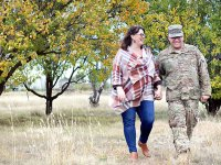 Janine Romero and her husband, Lee, walk through a dry grassy area holding hands. Janine is looking at Lee and both are smiling. Janine wears blue jeans and a red-toned plaid shirt and Lee wears his military uniform.