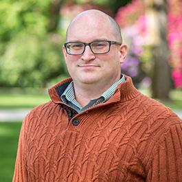Oregon State Ecampus Testing Coordinator Jeff Buckley wears an orange sweater.