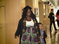 Jennifer Ware walks proudly with her young son holding her hand on her graduation day.