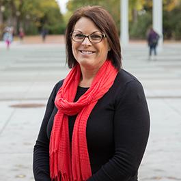 Karen Johnston's headshot. She wears a black long-sleeved shirt and red scarf.