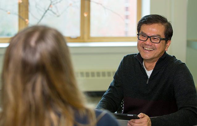 Counseling Academic Unit program chair and professor of counseling education , Kok-Mun Ng. He is seated and smiling while talking to a person seated across from him.