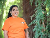 Luhui Whitebear, the assistant director of Oregon State University's Native American Longhouse Eena Haws, stands amid a group of trees on campus.