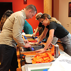 Orman leans over a table where he and several other students are screen printing T-shirts at an event hosted by the Native American Longhouse Eena Haws.