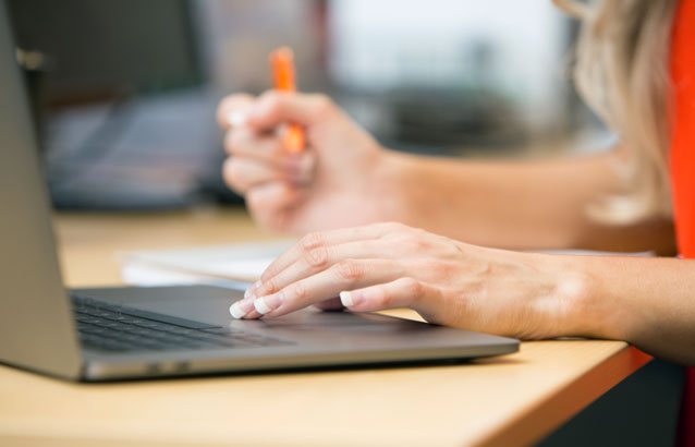 A close-up of a student using a laptop. Their left hand rests on the laptop's touchpad, while their left hand holds a pencil over a piece of paper.