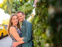 Ryan Fox and his fiancée, Liz, pose with their arms around each other near a tall hedge.