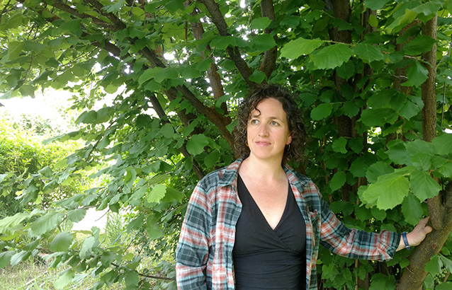 Oregon State Ecampus sociology alumna Sarah Brown stands with one hand resting on the branch of a tree.
