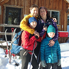Sarah and her family dressed in thick coats and hats near a wooden lodge while on their annual ski trip in the Methow Valley.