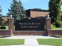 "A large black sign surrounded by red brick that reads ""Oregon State University"" in white lettering."