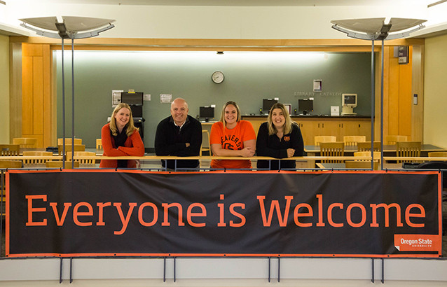 "Four Oregon State Ecampus student success counselors lean with their arms crossed on an indoor balcony in the Valley Library. Hanging from the balcony below them, an orange and black sign reads ""Everyone is Welcome."""