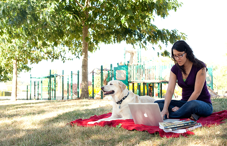 A student sits with their yellow labrador on a red blanket at a park. They are looking at a silver laptop and there is a stack of textbooks nearby.